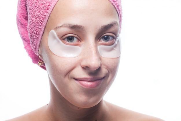 Привлекательная усмехаясь молодая женщина с белыми заплатами под глазами и розовое полотенце на ее голове изолированной на белизне. портрет крупным планом. уход за кожей