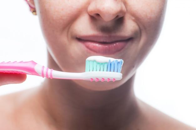 彼女の歯を磨く美しい女性をクローズアップ。朝のトリートメント