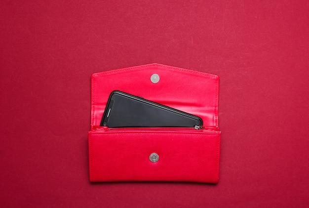 Смартфон в красном кожаном кошельке на красном. вид сверху
