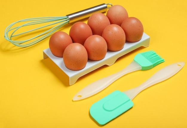 Силиконовые кухонные инструменты (шпатель, кисточка и венчик), лоток для яиц на желтом.