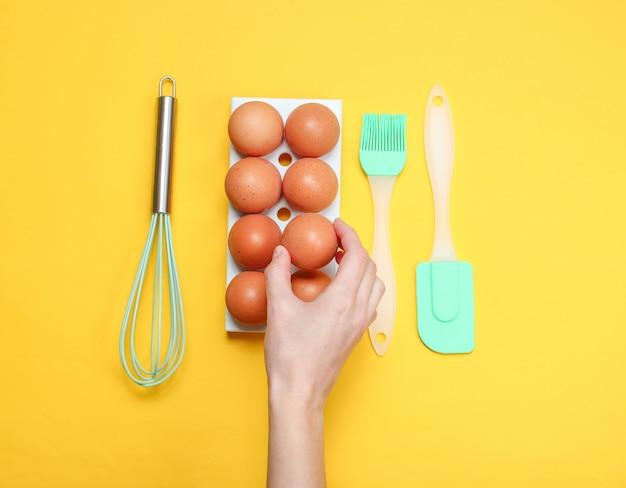 Женская рука принимая куриное яйцо из яйца лоток на желтый.