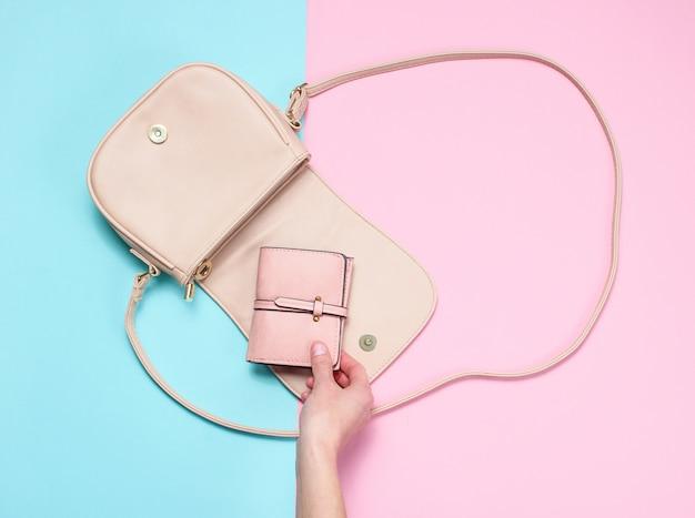 Женская рука берет кожаный кошелек из сумки на пастель. вид сверху, плоская планировка