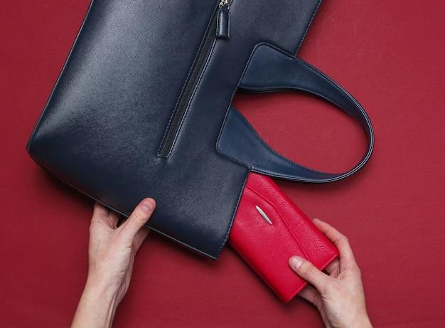 Женская рука положила в кожаную сумочку красный кошелек на темно-красном. вид сверху, плоская планировка
