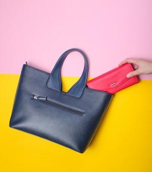 Женская рука берет красный кошелек из кожаной сумки на пастель. вид сверху, плоская планировка