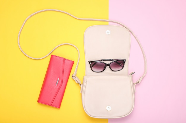 Кожаная сумка, модные солнцезащитные очки, красный кошелек на пастельной цветной бумаге. вид сверху. плоская планировка