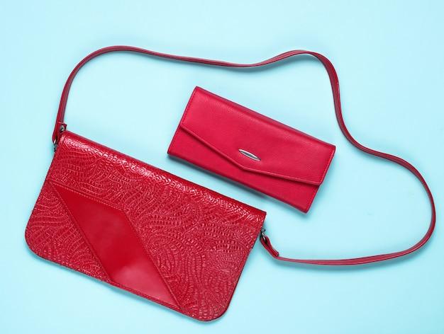 Красная кожаная сумка в стиле ретро и кошелек на синем, вид сверху
