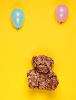 Мягкий плюшевый мишка с воздушными шарами на желтом фоне. минимализм.