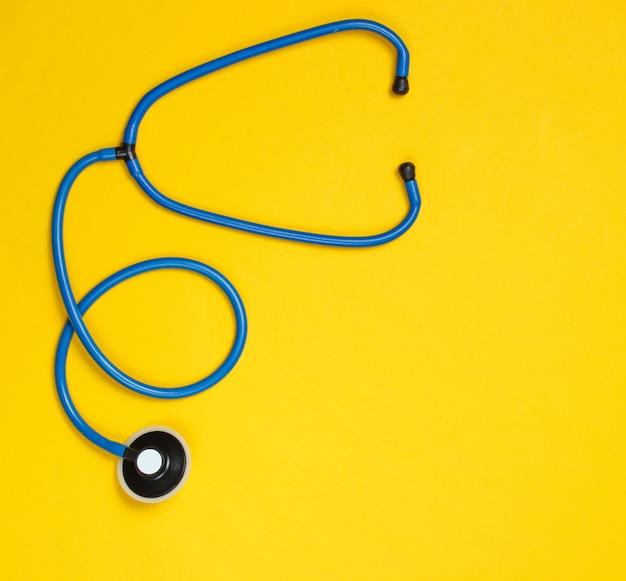 黄色の紙の背景に青い医療聴診器。