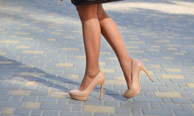 女の子は通りに沿ってかかとを歩いています。かかとのクローズアップで女性の足。ストリートファッション。