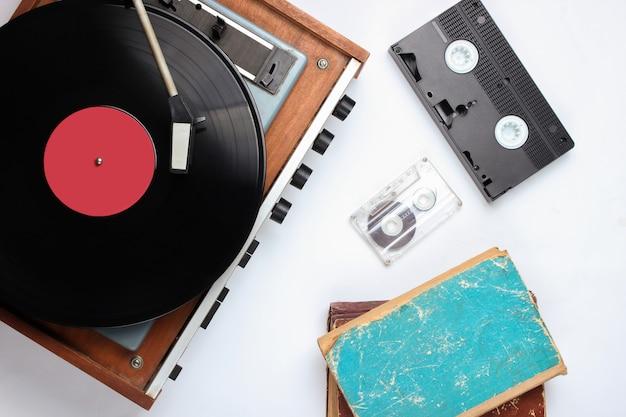 白のポップカルチャーのレトロなオブジェクト。ビニールレコードプレーヤー、古い本、オーディオ、ビデオカセット。