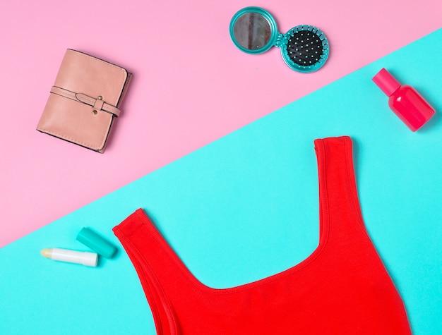赤いシャツ、財布、化粧品は、多色のパステルカラーの表面に配置されています。女性のアクセサリー。ファッショナブルな外観。平干し。