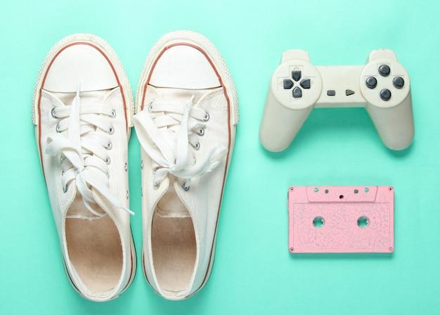古いスニーカー、ゲームパッド、オーディオカセット。ミント色の背景のポップカルチャー属性。ミニマリズム、トップビュー