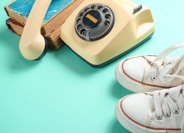 Старые кроссовки, ретро телефон и стопка старых телефонных книг на мятном цветном фоне