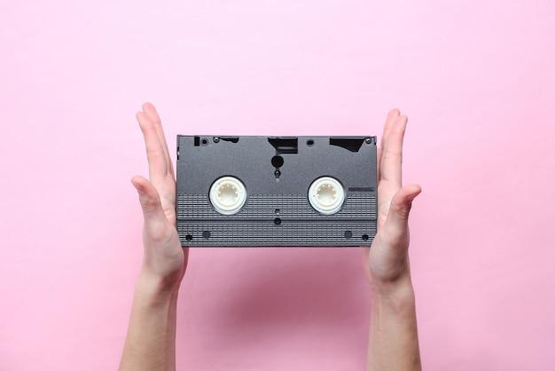 女性の手は、ピンクのパステル調の背景にビデオカセットを保持しています。レトロなスタイル、ポップカルチャー、ミニマリズム、トップビュー