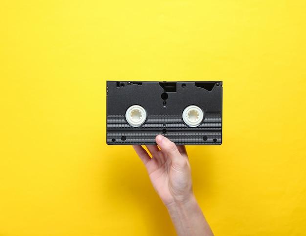 女性の手は、黄色の背景にビデオカセットを保持しています。レトロなスタイル、ポップカルチャー、ミニマリズム、トップビュー