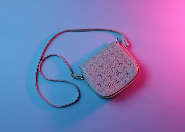 ファッショナブルな革のバッグ、青赤ネオンライトの上面写真