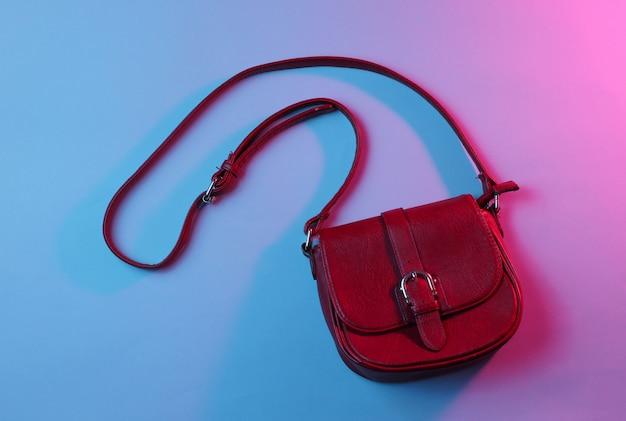 ブルーピンクのレトロなネオンライトとおしゃれな赤い革のバッグの上面写真