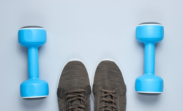 タイムスポーツ。プラスチック製の青いダンベル、灰色のスポーツシューズ。
