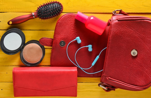 女性用バッグには何が入っていますか?赤いバッグ、革製の財布、ヘッドフォン、ミラー、櫛、黄色の木製テーブルの上の香水瓶。上面図。