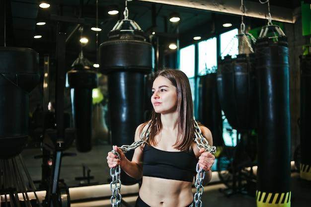 若いフィット彼女の肩に重金属チェーンでポーズスポーツウェアで女性