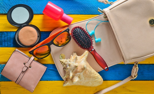 女性用バッグには何が入っていますか?夏のビーチアクセサリー、シェル。バッグ、革製の財布、ヘッドフォン、ミラー、櫛、香水瓶、黄色の青い木製のテーブル。上面図。