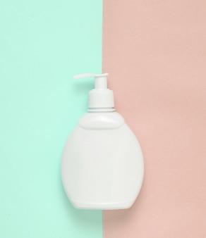 Белая бутылка крема на синем розовом фоне пастельных