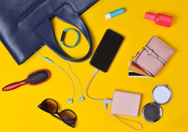 女性のアクセサリーは、明るいオレンジ色の表面に配置されています。バッグ、化粧品、スマートフォン、スマートウォッチ、外部バッテリー、ヘッドフォン、クレジットカード付き財布。女性用バッグには何が入っていますか?上面図。