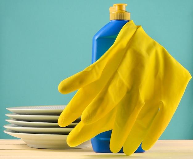 パステルブルーの背景に分離されたテーブルの上のお皿を洗うための製品
