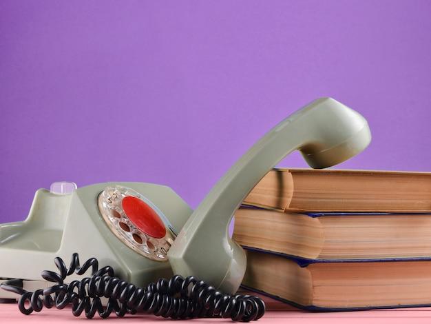 Ретро роторный телефон, стопка книг на столе, изолированных на фоне пурпурной пастельной стены