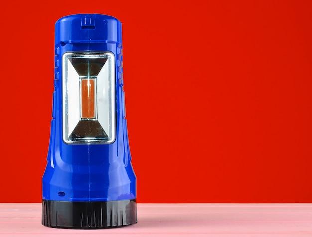 赤い壁に分離された机の上にある青い懐中電灯プロジェクター