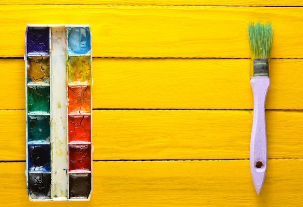 Палитра акварельной краски и кисти для рисования на желтых деревянных досках. вид сверху. копировать пространство художественная концепция.