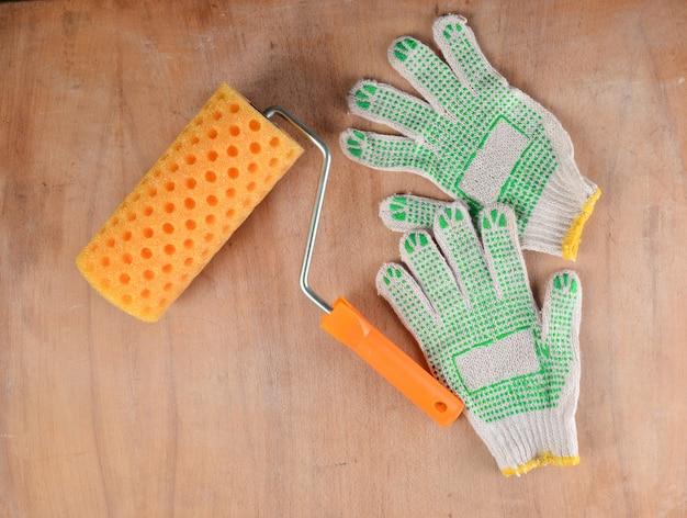 木製の背景にペイントローラーと作業用手袋
