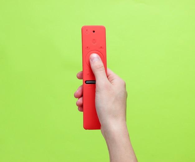 女性の手が緑色の背景でテレビのリモコンを切り替えます