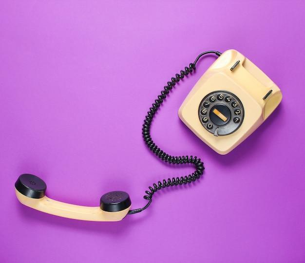 Ретро роторный телефон с трубкой на фиолетовом фоне