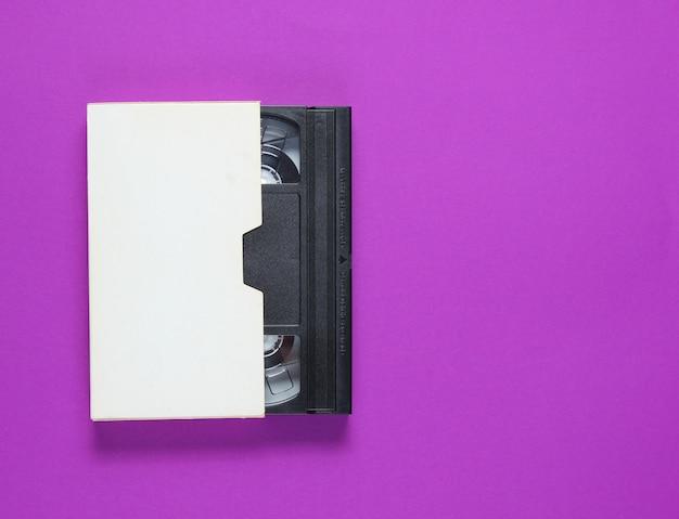 紫色の背景に紙ケースのビデオテープ