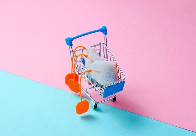 Чайные пакетики в игрушечной тележке на пастельном фоне