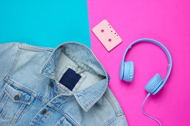 青ピンクの背景にデニムジャケット、ヘッドフォン、オーディオカセット