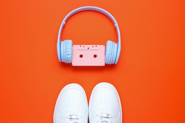 オレンジ色の背景にオーディオカセット、白いスニーカー付きヘッドフォン