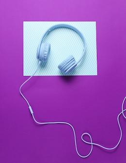 Синие наушники с кабелем на синем фиолетовом фоне творческого