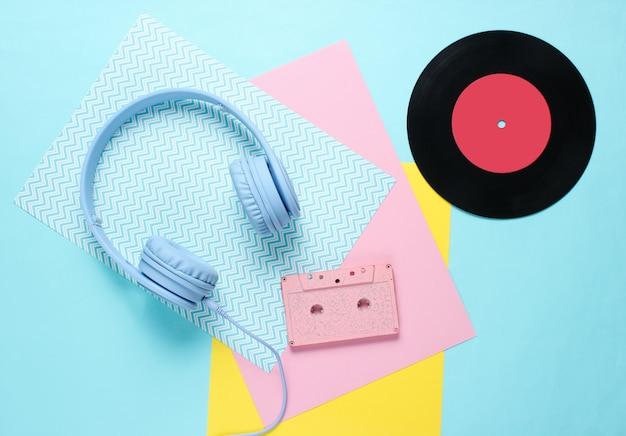 色紙の背景にオーディオカセット付きのヘッドフォンとイヤホン。
