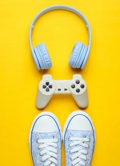 ヘッドフォン、黄色の背景にスニーカーとゲームパッド