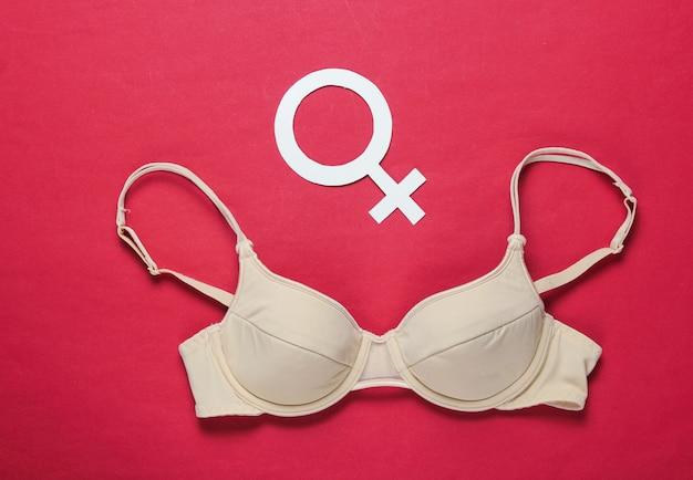 Концепция феминизма. женский бюстгальтер, гендерный символ на красном столе. вид сверху, минимализм