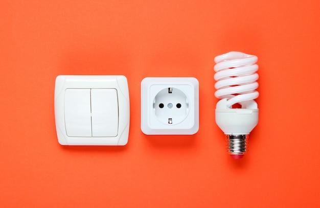 経済スパイラル電球、電気プラグ、スイッチ。上面図。ミニマリズムエレクトロコンシューマーコンセプト