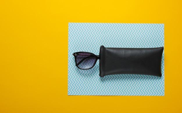 Модные солнцезащитные очки в защитном футляре на картонном столе. вид сверху