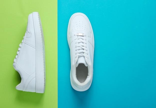 Модные белые кроссовки на двухцветном столе. вид сверху