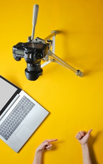 Блог минимальной концепции. вроде и подписка. женские руки ведут блог с камерой на штатив и ноутбук. вид сверху