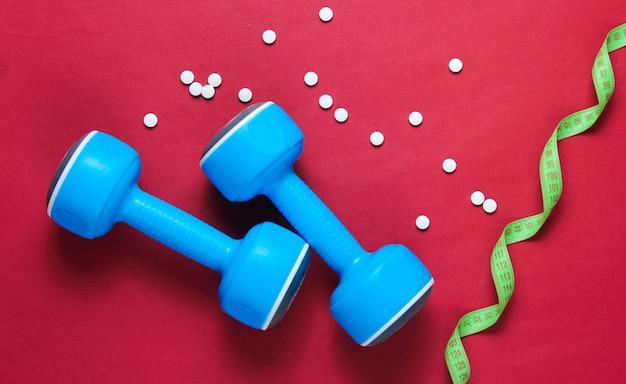 スポーツ減量の概念。ダンベル、定規、赤の背景の丸薬。ミニマリズム。上面図