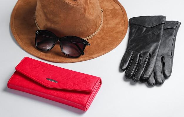 レディースファッションアクセサリー。赤い革の財布、サングラス、手袋のクローズアップ