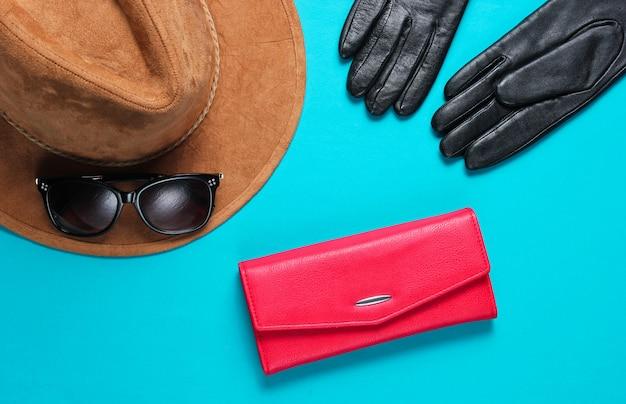レディースファッションアクセサリー。赤い革の財布、サングラス、青いテーブルの上の手袋のクローズアップ