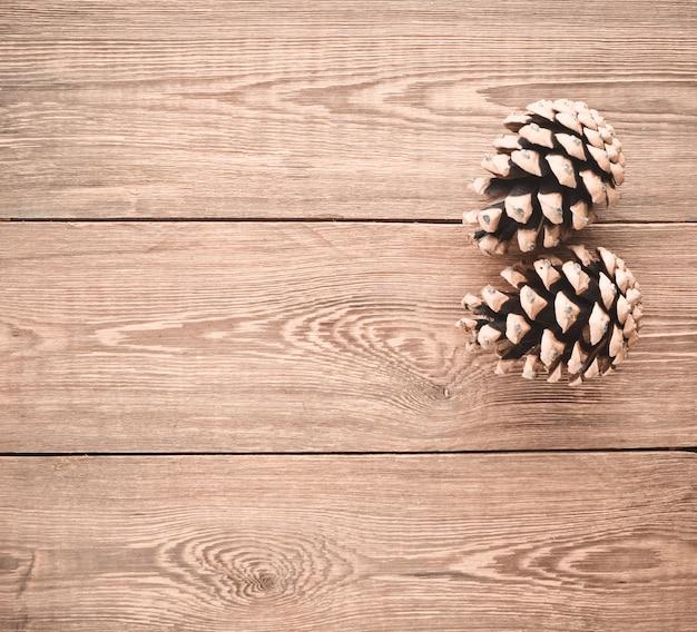 Две сосновые шишки на деревянном столе. рождественская тайна. копировать пространство
